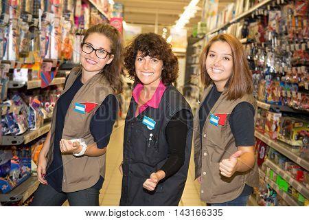 Happy staff team with women in a supermarket