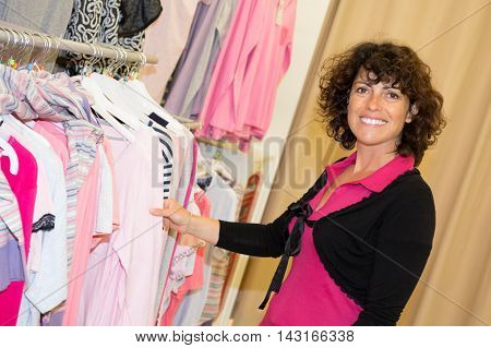 Woman Choosing Dress During Shopping At Garments Apparel Clothing Shop