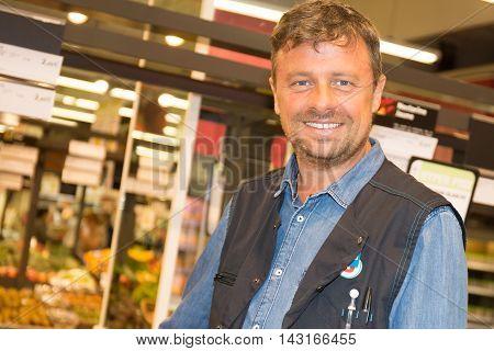 Shop Assistant In A Supermarket At The Vegetable Shelf