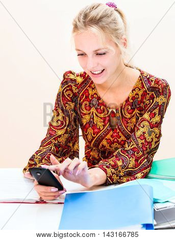 Young Woman At Work Looks At The Phone