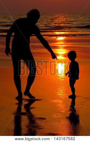 A silhouette father telling his son to watch his step on the beach metaphorically implying to watch his step in life ahead.