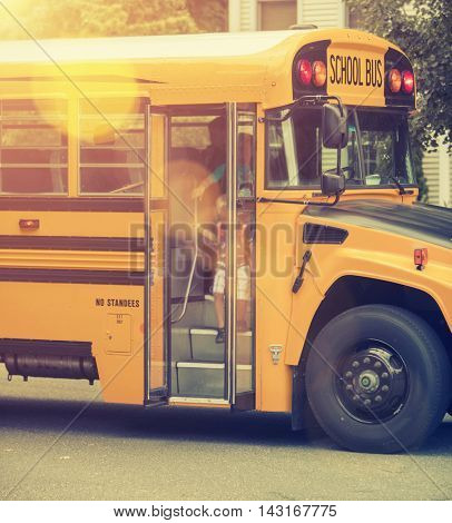 A group of young children getting off the schoolbus