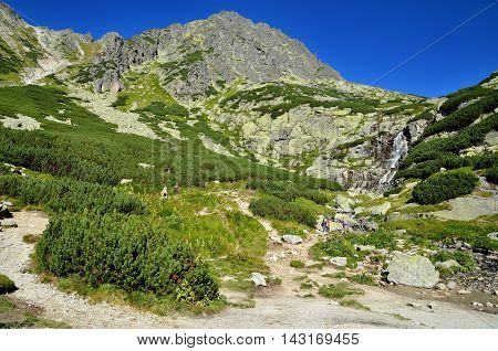 HIGH TATRA SLOVAKIA - AUGUST 20 2015: Tourists on a mountain trail to the waterfall in the background.