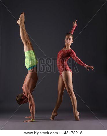 Studio photo of sports gymnasts posing at camera, on gray backdrop