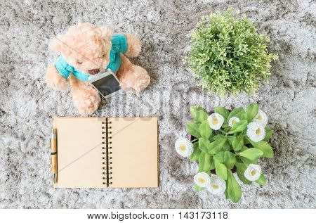 Closeup brown note book diary with blank brown paper space at page with brown pen with artificial plant and bear doll on gray carpet floor textured background