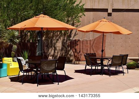 Patio with outdoor furniture including tables, chairs, and umbrellas