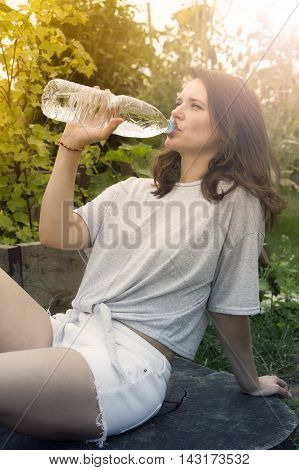 young woman in shorts sitting in garden and drinking water