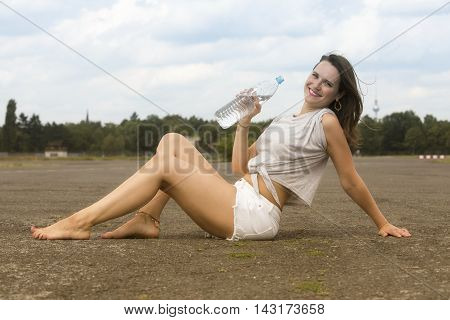 young woman in shorts sitting on pavement with a bottle of water