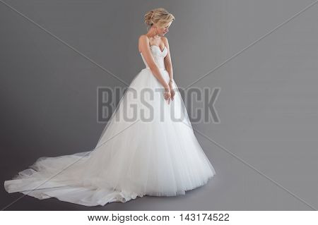 Charming young bride in luxurious wedding dress. Emotions of happiness, laughter and smile, gray background, place for your text on the right