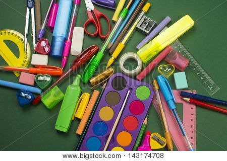 Different school supplies are on green background.