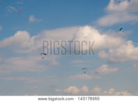 skydivers against the blue sky with white clouds