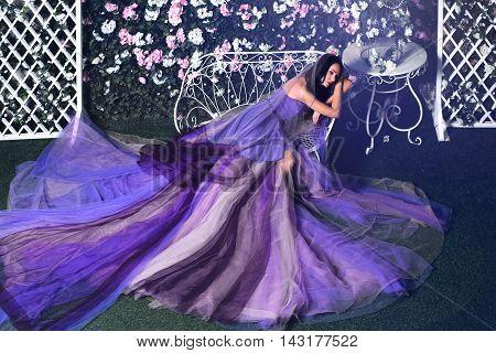 Beautiful brunette woman wearing long purple dress sitting on the bench in a flower garden