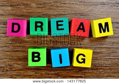Dream Big on wooden table close up