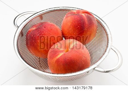 Peaches with morning dew in a stainless steel colander isolated on a white surface