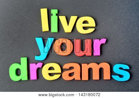 Text Live your dreams on black background