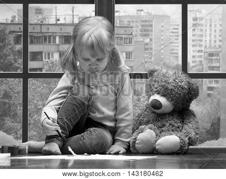 Little girl draws paints and brush. A huge window behind the glass city snow winter. toy teddy bear sitting next to. Black and white image