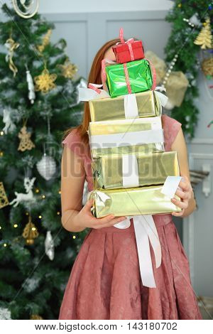 Girl teenager in dress holds many gifts in boxes in room with christmas decorations