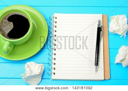 Notepad with crumpled paper and coffee on table