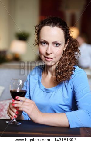 Woman in blue dress holds glass of red wine in restaurant, shallow dof
