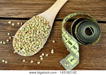 Buckwheat in wooden spoon with centimeter on table