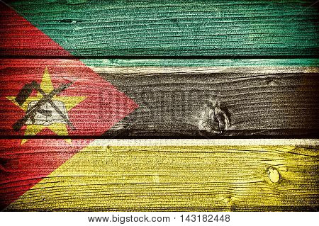 flag of Mozambique painted on old grungy wooden background: 3d illustration