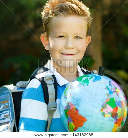 Cute boy is holding globe - education concept