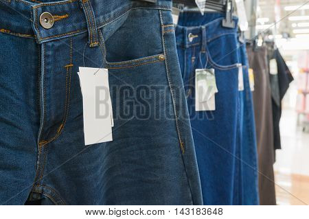 Blank White Tag Over The Blue Jeans On Hanger Shelf In Supermarket