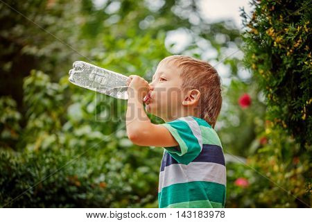 Little boy drinking mineral water from the plastic bottle in the park.