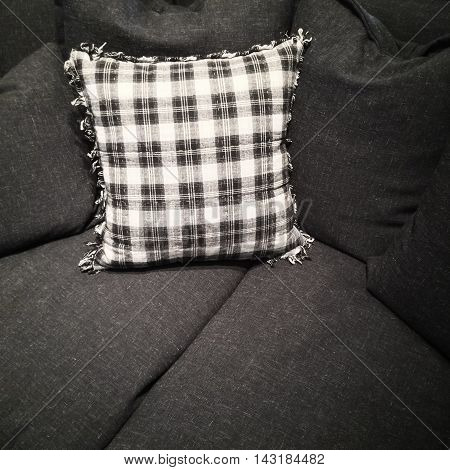 Stylish black and white checked cushion on a dark gray sofa.