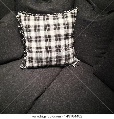 Stylish black and white checked cushion on a dark gray sofa.