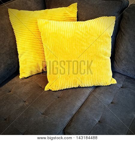 Bright yellow cushions decorating a gray sofa.