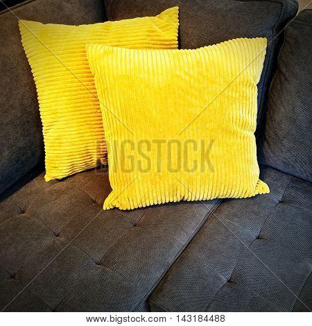 Bright yellow cushions decorating a gray sofa.