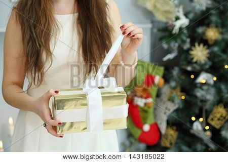 Hands of girl opening gift in box near christmas tree inj decorated room