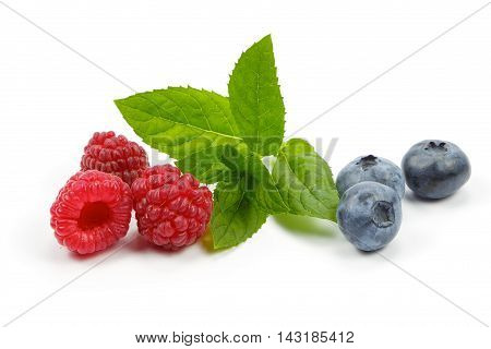 Raspberries and blueberries with mint on white background