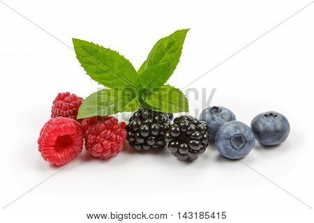 Raspberries blueberries and blackberries with mint on white background