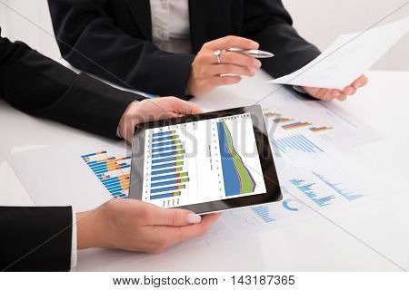 Close-up Of Businesspeople Comparing Graphs On Digital Tablet In Office