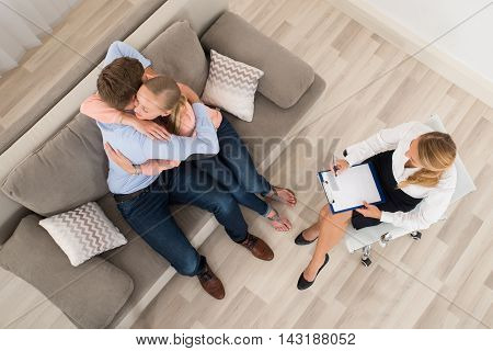 Elevated View Of Young Couple Sitting On Sofa Embracing In Front Of Female Psychologist