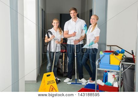 Portrait Of A Happy Young Janitors Standing In Corridor