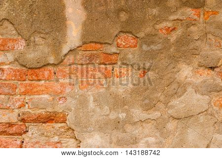 Old orange brick wall with rough cement