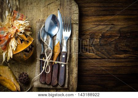 Autumn Halloween Thanksgiving composition. Halloween pumpkin and autumn rustic set of cutlery knife, spoon, fork, tea spoon on rustic cutting board wtih autumn yellow leaves. Copy space. Top view