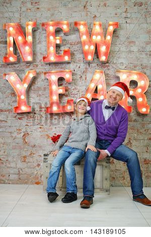 Father with son in red santa caps sit near big letters New Year in studio