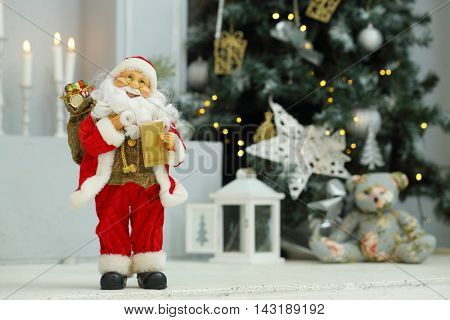 Little Santa Claus near christmas tree with decorations and candles in studio