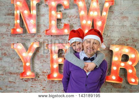 Father with son in red santa caps pose near big letters on wall