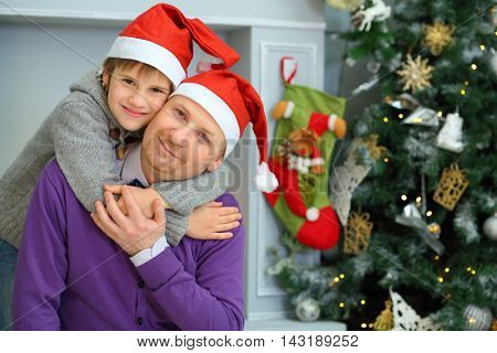 Happy handsome father with son in santa caps pose near christmas tree