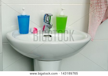 Bathroom interior with white sink and faucet two colorful spray bottle for detergent cleaning products bottle brush and towel