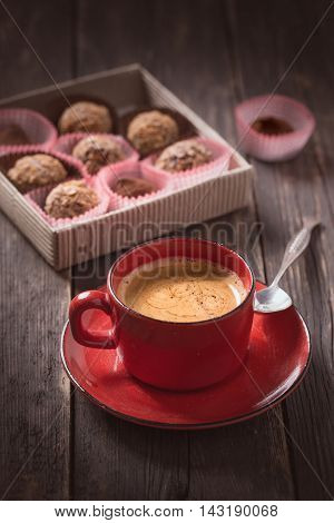 Coffee cup and truffles on dark background