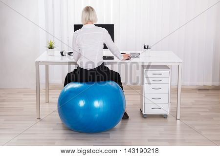 Businesswoman Sitting On Fitness Ball Working In Office