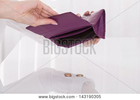 Close-up Of Woman Holding Empty Purse With Coins On Desk
