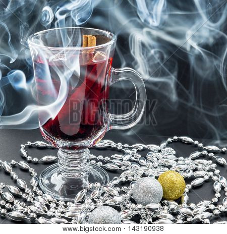 Transparent cup of Mulled wine smoke and christmas decoration on black background
