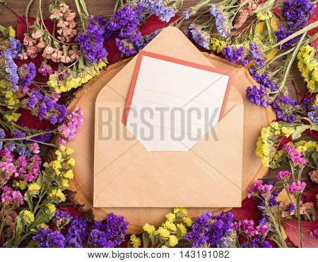 Dried multicolored statice flowers around envelope with empty card